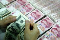 Банковский служащий пересчитывает доллары рядом с пачками юаней