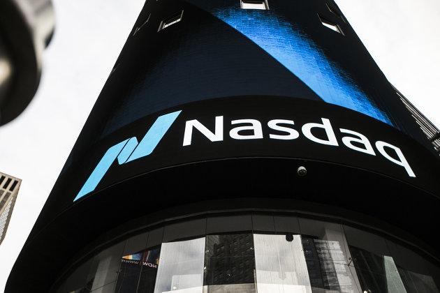 Информационная панель биржи NASDAQ на первых этажах небоскрёба Конде-Наст-билдинг на Таймс-сквер в Нью-Йорке