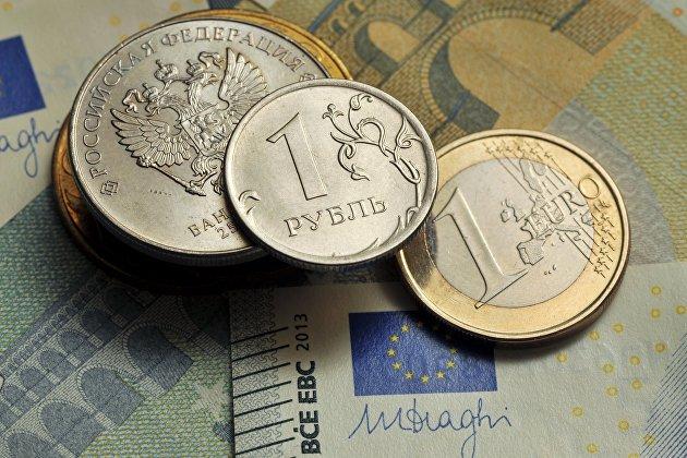 Монеты номиналом 1 рубль и 1 евро на фоне банкноты номиналом 5 евро