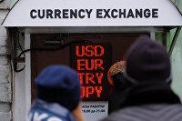 Люди стоят у обменника валют