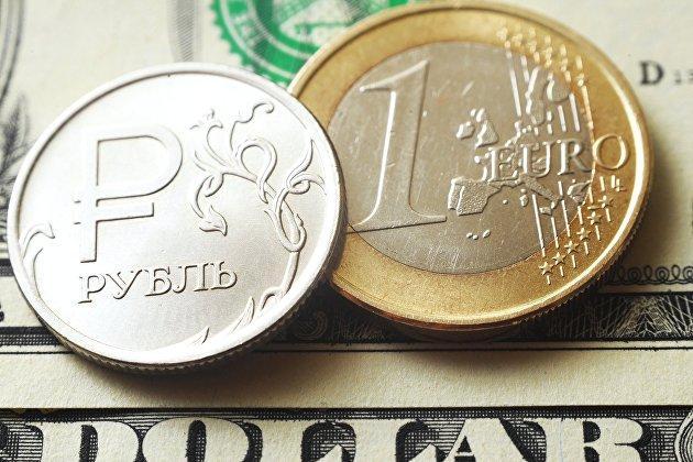 Монеты номиналом один рубль и один евро на банкноте один доллар США